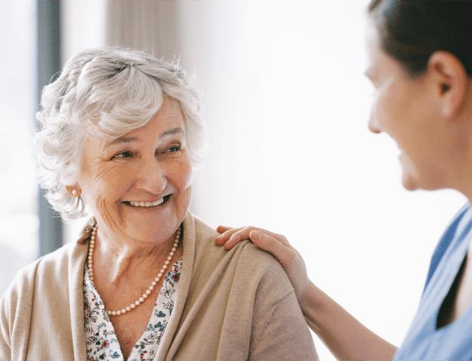 senior woman smiling at her caretaker
